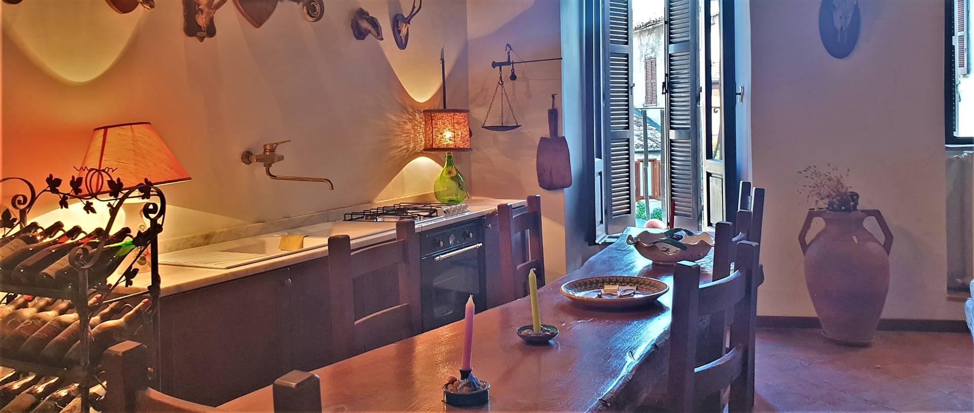 sala con camino e cucina a vista