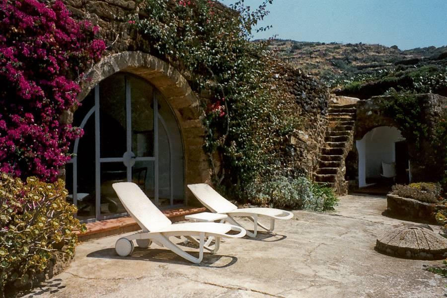 """Questa residenza regala un'atmosfera magica fuori dal tempo. Gli antichi dammusi nascosti tra i rampicanti e i """"giardini panteschi"""" con la loro forma"""