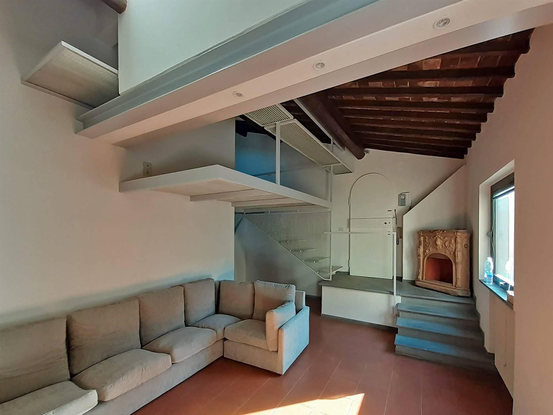 soggiorno open space con soppalco d'arredo