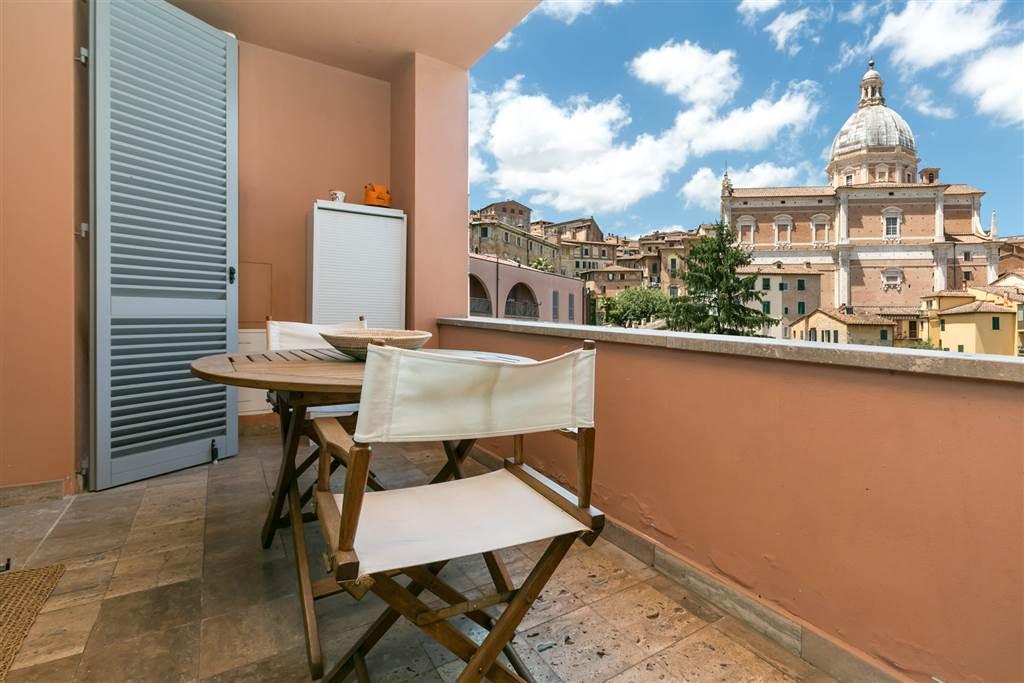 Confortevole bilocale di mq 57 con terrazza di circa mq 7 con vista meravigliosa su uno dei monumenti più suggestivi del centro storico senese. L'appartamento si trova in un condominio moderno dotato