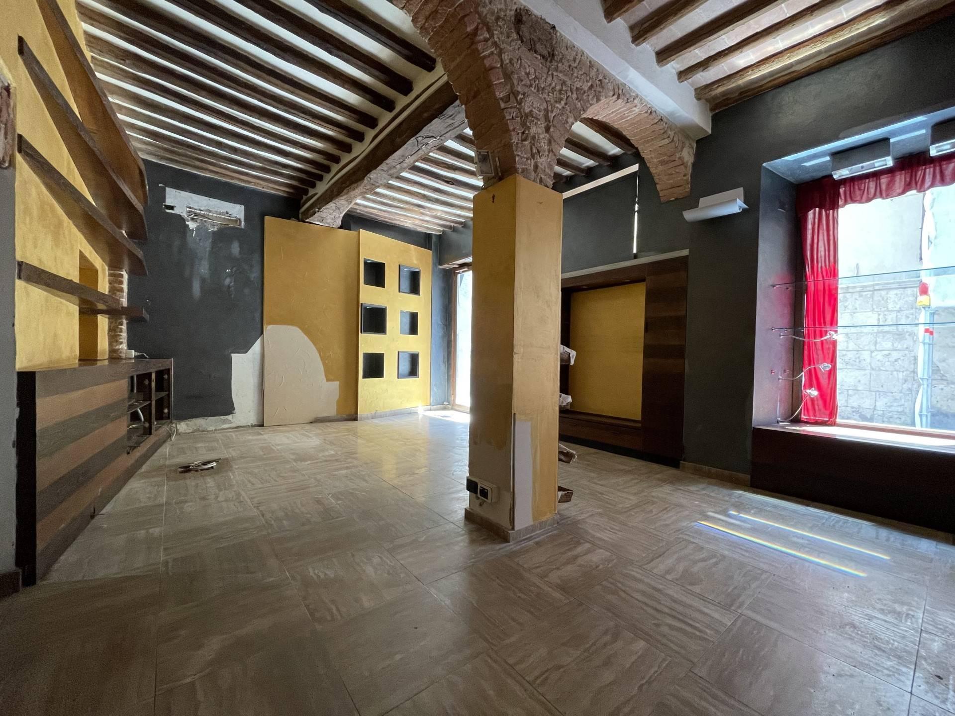 Nel centro storico di Siena, in Via della Sapienza, locale commerciale ristrutturato in locazione con due ampie vetrine e composto da una prima parte